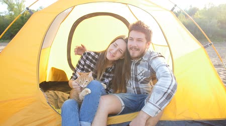 materiaŁ : Young Happy couple with cat sitting in tent during hiking trip Wideo
