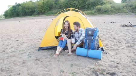 Young Happy couple with cat sitting in tent during hiking trip Stock mozgókép