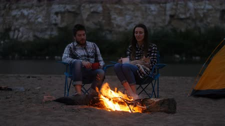 камин : Travel and love concept. Young Lovely couple near fireplace on camp