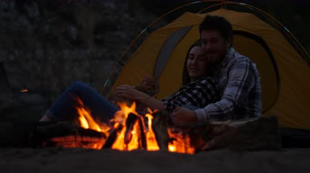 Travel and love concept. Young Lovely couple near fireplace on camp