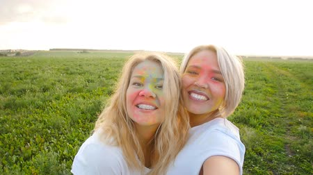 Friendship concept. Girlfriends make selfie in paints of holi
