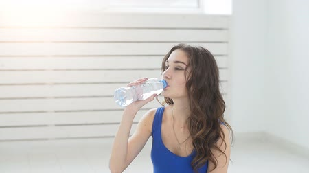 Young woman relaxing after training routine in gym hall, resfreshing herself with drinking water indoors Stock mozgókép