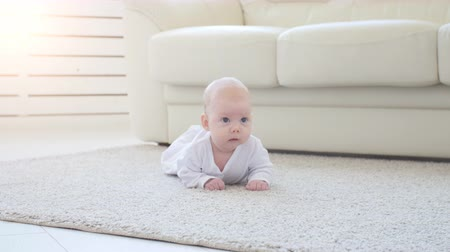 interiér : Cute funny baby lying on a beige carpet