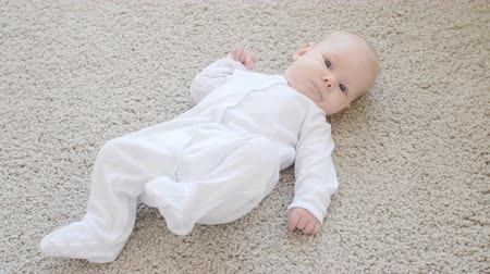 enfermaria : Cute funny baby lying on a beige carpet