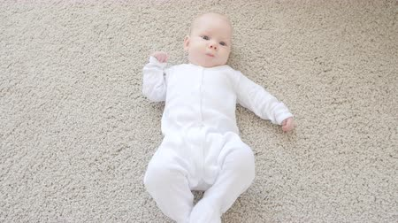 Cute funny baby lying on a beige carpet