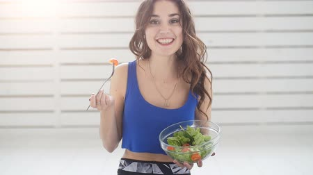 Healthy lifestyle concept. Smiling sporty young woman with green salad at home Stock mozgókép