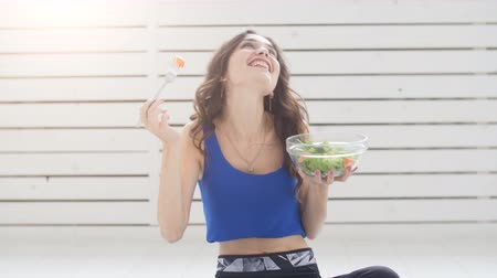 Healthy lifestyle concept. Smiling sporty young woman with green salad at home Stock Footage