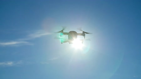 Concept of personal drones and aerial photography. Quadcopter flying overhead in cloudy blue sky Stock Footage
