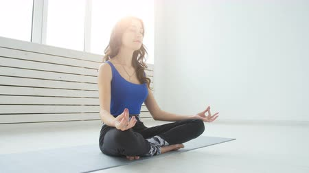 pain free : Yoga and home workouts concept. Young woman meditates while practicing yoga indoors
