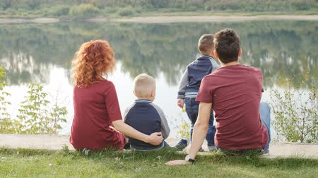 Family and children concept. Young couple with two sons walking by the river
