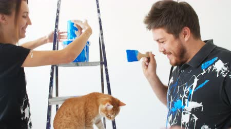 swatches : The concept of new real estate. Young couple with cat painting and renovation a room in their new house Stock Footage