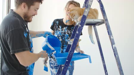 The concept of new real estate. Young couple with cat painting and renovation a room in their new house Stock mozgókép
