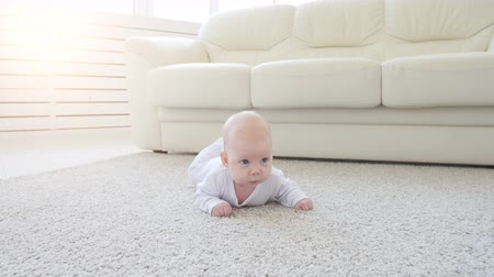 Happy Baby Lying on Carpet Background, Smiling Infant Kid girl in White Clothing