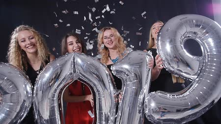 champagne flute : Happy New Year concept. Group of young women are having fun and holding bigger numbers 2019 Stock Footage