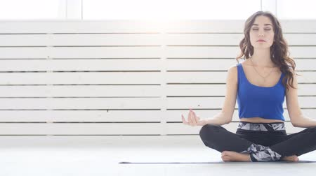 restorative : Sporty young woman practicing yoga, sitting in Half Lotus exercise, Siddhasana pose, indoor, home interior background