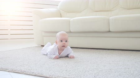 knitted : Concept of children and parenthood. Cute Happy Baby is Lying on Carpet Stock Footage