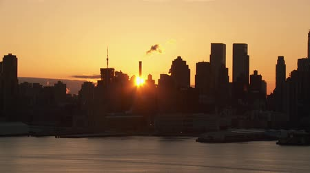 небоскреб : The sun rises behind the buildings of the Manhattan skyline of New York City in a timelapse sequence as viewed over the Hudson River looking east from New Jersey.