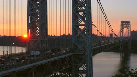 napfény : The sun rises as morning rush hour traffic on the George Washington Bridge crosses the Hudson River between New Jersey and New York. Stock mozgókép