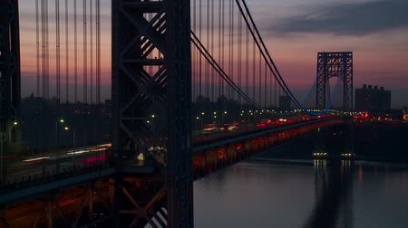fort lee : (Time-lapse) Morning rush hour traffic on the George Washington Bridge crossing the Hudson River between New Jersey and New York just before sunrise. The bridge was illuminated in blue lights in support of Autism Awareness.