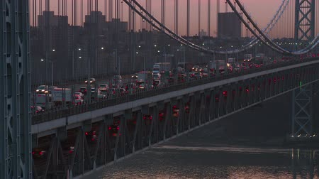 fort lee : Morning rush hour traffic on the George Washington Bridge crosses the Hudson River between New Jersey and New York just before sunrise. The bridge was illuminated in blue lights in support of Autism Awareness.