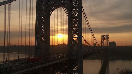 north america : The sun rises as morning rush hour traffic on the George Washington Bridge crosses the Hudson River between New Jersey and New York. Stock Footage