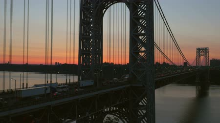 fort lee : Morning rush hour traffic on the George Washington Bridge crosses the Hudson River between New Jersey and New York just before sunrise. Stock Footage