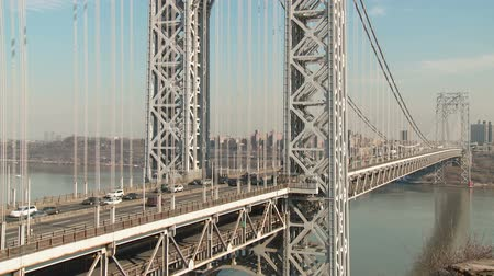 fort lee : (Time-lapse) Afternoon traffic flows over the George Washington Bridge high over the Hudson River, as viewed from Fort Lee, New Jersey. Jeffreys Hook Lighthouse is visible on the other side of the river in Fort Washington, New York. Stock Footage