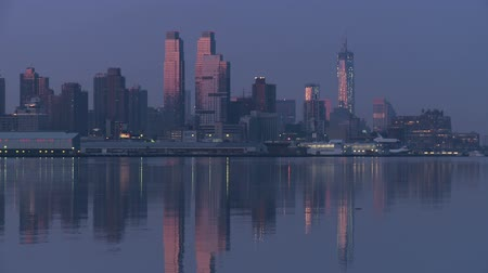 ад : Buildings on the West Side of Manhattan, from approximately 54th Street to just south of the Intrepid Sea, Air and Space Museum, and their reflections on the Hudson River during the last hour before sunrise. Space Shuttle Enterprise is visible on the deck