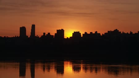 wschód słońca : (Time-lapse) Sunrise over the West Side of Manhattan and the Hudson River in New York City.