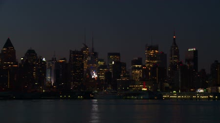 západ : The mid-town Manhattan skyline remains illuminated with lights reflecting off the surface of the Hudson River during the last hour before sunrise in New York City.