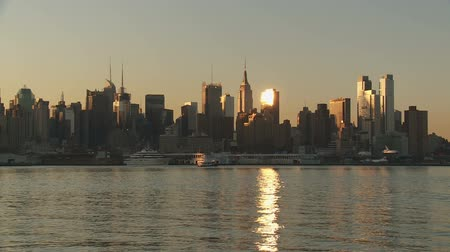západ : The mid-town Manhattan skyline is lit by sunlight just after sunrise in New York City.