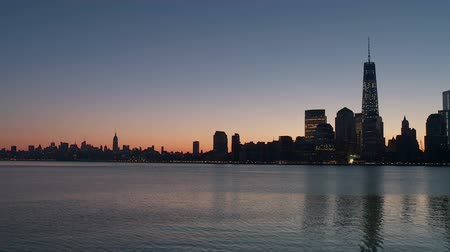 império : The Freedom Tower, part of the new World Trade Center complex, rises over the skyline of lower Manhattan looking north up the Hudson River toward midtown during morning twilight in New York City. Stock Footage
