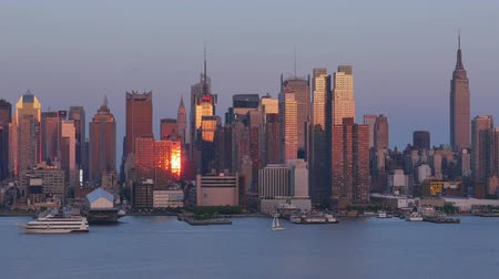 urban skyline : Sunset approaches as the sun and orange colored western sky is reflected off the windows of the mid-town Manhattan skyline over the Hudson River during late afternoon.