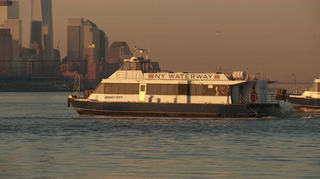 feribot : WEEHAWKEN, NJ - APRIL 4: NY Waterway ferries leave the Port Imperial Ferry Terminal during the morning rush hour headed for Manhattan on April 4, 2013 in Weehawken, New Jersey. Stok Video