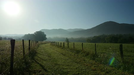 farpado : The rising sun shines over a road between two barbed-wire fences as early morning fog still hangs over Cades Cove in Great Smoky Mountains National Park.