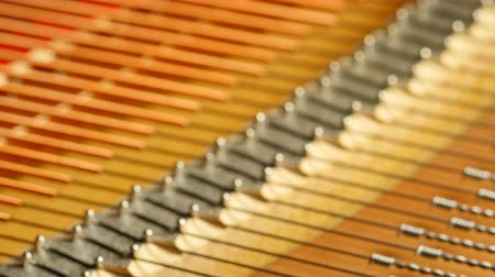 пианино : Push-in shot of bass bridge and strings of a grand piano pushed into focus.
