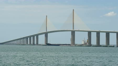 tampa bay : Traffic crosses the Sunshine Skyway Bridge over Tampa Bay as a tugboat pushes a barge underneath, as viewed from the south fishing pier.