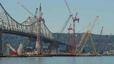 pozisyon : A towboat moves a barge crane into position for work on construction of the New Tappan Zee Bridge over the Hudson River between Westchester and Rockland counties. Stok Video