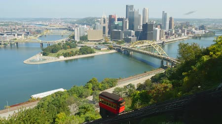 inclinado : The Duquesne Incline ascends Mt. Washington with a view of the downtown area including the skyline, bridges, and Point State Park at the confluence of the Allegheny and Monongahela Rivers in Pittsburgh, Pennsylvania.