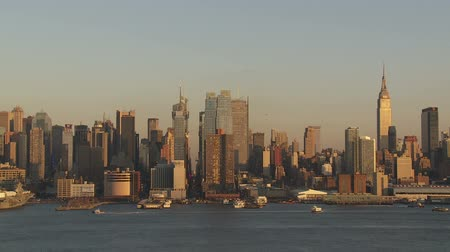 império : (Time-lapse) Boat and ferry traffic on the Hudson River in front of the mid-town Manhattan skyline in New York City during late afternoon. Stock Footage