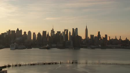 império : Wispy cirrus clouds roll over the Manhattan skyline of New York City shortly after sunrise in a time-lapse sequence.