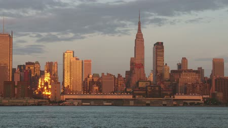 império : A view of the Empire State Building, Hudson River, and mid-town Manhattan skyline in New York City during late afternoon.