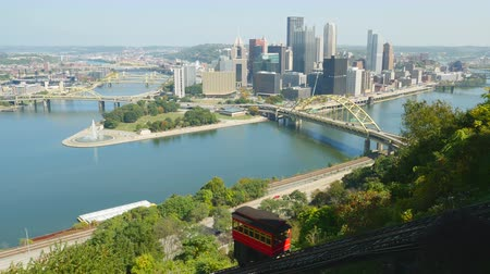 состояние : The Duquesne Incline descends Mt. Washington with a view of the downtown area including the skyline, bridges, and Point State Park at the confluence of the Allegheny and Monongahela Rivers in Pittsburgh, Pennsylvania. Стоковые видеозаписи