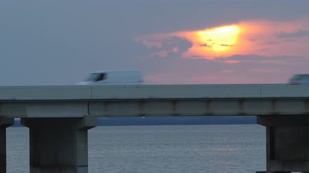 tampa bay : The sun rises over Tampa Bay as traffic crosses the Sunshine Skyway Bridge, as viewed from the south fishing pier.