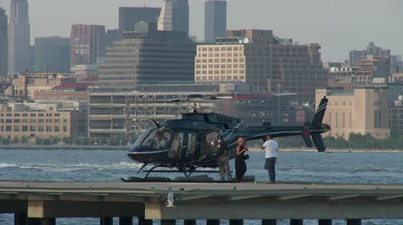 heliport : JERSEY CITY - JUNE 23: A ground crew member helps passengers get off a helicopter at the Paulus Hook Pier Heliport on June 23, 2013 in Jersey City.