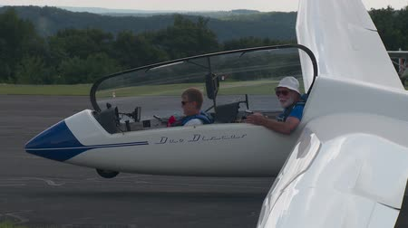 bezmotorové létání : ELMIRA, NY - JULY 31: Pilot Roy McMaster and passenger prepare to exit their sailplane after landing during the 2013 SSA Region 3 Soaring contest at Harris Hill gliderport on July 31, 2013 in Elmira, New York.