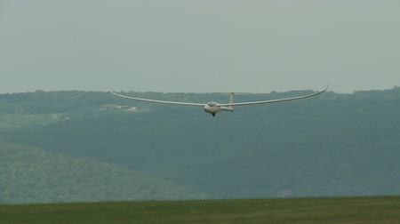 bezmotorové létání : ELMIRA, NY - AUGUST 2: Pilot Tim Hanke brings his Discus 2a sailplane in for a landing during the 2013 SSA Region 3 Soaring contest at Harris Hill gliderport on August 2, 2013 in Elmira, New York. Dostupné videozáznamy