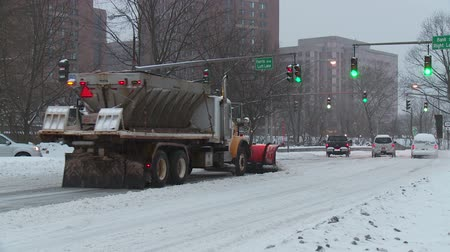 kuzey amerika : WHITE PLAINS, NY - FEBRUARY 5: Cars head into the city center on snowy Tarrytown Road (NY Route 119) as a Public Works snowplowsand spreader passes after a heavy snowfall on February 5, 2014 in White Plains.