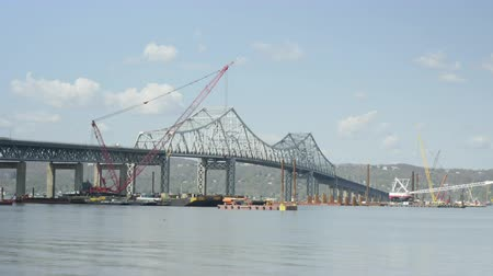 kuzey amerika : TARRYTOWN, NY - MAY 2: (Time-lapse) Barges and cranes on the Hudson River, under the existing Tappan Zee Bridge, help to lay the pilings for the foundation of the new bridge on May 2, 2014 in Tarrytown. Stok Video