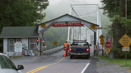 kolektor : DINGMANS FERRY, PA - AUGUST 5: Commuters stop and pay the toll before crossing Dingmans Ferry Bridge on August 5, 2014 in Dingmans Ferry, Pennsylvania. The bridge crossed the Delaware River from Pennsylvania to New Jersey. Dostupné videozáznamy